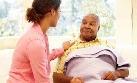 caregiver and elderly man in bed talking